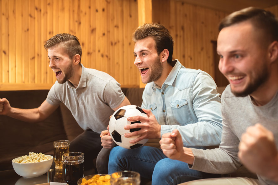 Three guys in a prefab cabin cheering at a soccer match on tv.